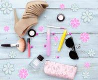 Schuhe, Hut, Sonnenbrille, Parfüm, Tinte, Lidschatten, Blumen, Lippenstift, Make-upbürste, erröten, Draufsicht über einen blauen  Stockfotografie