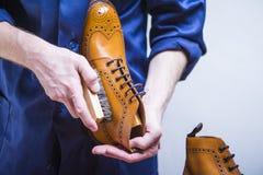 Schuhe-Ideen Nahaufnahme von bemannt Hände mit Reinigungs-Bürste lizenzfreies stockfoto