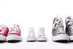 Schuhe im Vater groß, Muttermedium und Sohn oder kleine Größe der Tochter Kinderim Familienliebeskonzept Stockfoto