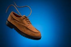 Schuhe mit einen fliegende lederne Booten des Weizens oder des braunen nubuck mit Fliegenspitzeen auf einem blauen Hintergrund Stockfotos