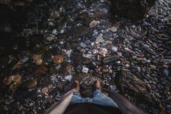 Schuhe oben an vom Felsen mit Wasser lizenzfreie stockbilder