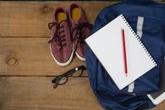 Schuhe, Schauspiele, Buch, Bleistift, digitale Tablette und Schultasche auf Holztisch Stockfotos