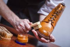 Schuhe-Sorgfalt-Ideen Nahaufnahme von bemannt Hände mit Reinigungs-Bürste lizenzfreie stockfotos