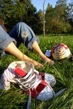 Schuhe und bloße Füße auf Gras Stockfotos