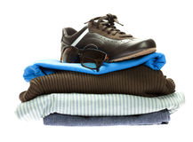 Schuhe und ein Berg der Kleidung getrennt auf Weiß Lizenzfreies Stockfoto