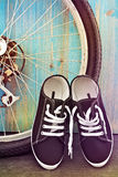 Schuhe und eine Fahrradfelge auf einem Hintergrund des blauen Bretterzauns Lizenzfreie Stockfotografie