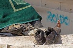 Schuhe und Füße des obdachlosen Mannes Stockfotos