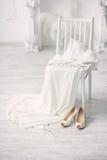 Schuhe und Hochzeitskleid auf Stuhl im Raum Stockfotos