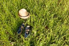 Schuhe und Hut auf Grashintergrund Stockbilder
