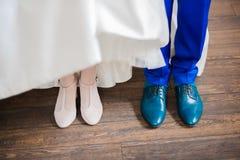 Schuhe von Hochzeitspaaren Die Braut mit einer Blume stockfotografie