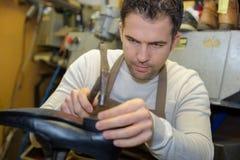 Schuhschuster, der Ferse auf Paarschuhen repariert lizenzfreies stockbild