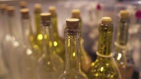 Schuif handbediend schot van flessen die gele kleur zich in een winkelplank bevinden die op klanten, close-up wachten stock video
