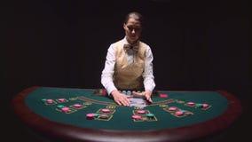 Schuifelt de casino professionele handelaar de pookkaarten en het uitvoeren van truc met kaarten Zwarte achtergrond Langzame Moti stock video