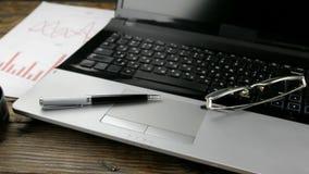 Schuifschot, close-up van Desktop, laptop, pen en glazen stock videobeelden