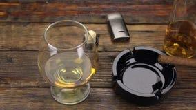 schuifschot Een sigaar in een asbakje en een glas van alcohol zijn op de oude lijst stock videobeelden