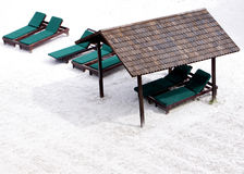 Schuilplaats en ontspannende ligstoel op wit zand Stock Foto's