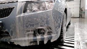 Schuim die van de bumper van de auto bij de autowasserette druipen stock footage