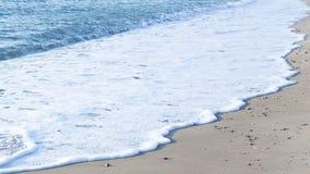 Schuim op het zand langs het overzees Stock Fotografie