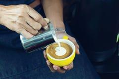Schuim van de Barista het gietende melk voor het maken van koffie latte kunst met patte royalty-vrije stock afbeelding