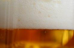 Schuimend bier als achtergrond in een glasmok stock fotografie