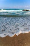Schuimend water op strand stock foto's
