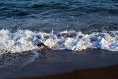 Schuimend zeewatergetijde op donker vulkanisch strand Het ontspannen overzeese golfbranding over kust stock afbeeldingen