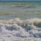 Schuimende golven op de kust Stock Afbeeldingen