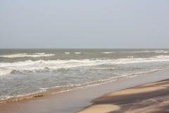 Schuimende golven op strand met patronen Stock Foto