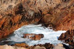Schuimende Overzees en Bruine Rotsen Stock Foto's