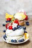 Schuimgebakjecake die met verse vruchten wordt verfraaid Stock Afbeelding