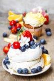 Schuimgebakjecake die met verse vruchten wordt verfraaid Stock Foto