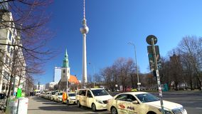 Schuine stand neer van Berliner Fernsehturm-Televisietoren aan taxis op Karl Liebknecht Strasse, Berlijn, Duitsland stock videobeelden