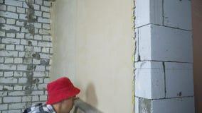 Schuine stand neer van bouwer het gladmaken pleister op binnenlandse muur met bouwheerser stock video