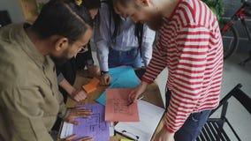 Schuine stand omhoog van Groep multi-etnische jonge medewerkers die op documenten met de bouw van plan letten die zich rond lijst stock footage