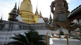 Schuine stand omhoog van het beeldhouwwerk van Boedha van reus in Groot Paleis en Wat Phra Kaew stock footage