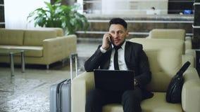 Schuine stand omhoog van zekere aantrekkelijke zakenman die mobiele telefoon spreken en laptop computer met behulp van terwijl bi stock video