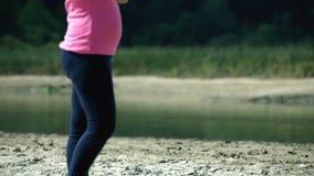 Schuine stand van blonde blootvoetse vrouw en rivierenrand die wordt geschoten stock footage