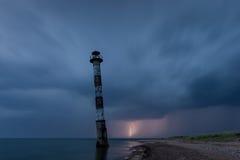 Schuine vuurtoren in de Oostzee Stormachtige nacht en bliksem Royalty-vrije Stock Afbeelding