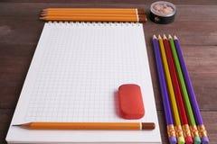 Schulübungsbuch mit bunten Bleistiften Lizenzfreie Stockbilder