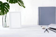Schul- oder Büroarbeitsplatz Minimalistic mit grauem Briefpapier auf weißem Hintergrund getrennte alte Bücher Stockbild