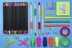 Schul- und Bürozubehör auf einem Hintergrund des blauen Papiers lizenzfreies stockfoto