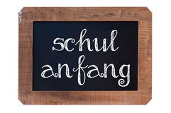 Schulanfang meaning Back to school written on a vintage blackboard with wooden frame isolated on white Stock Photos