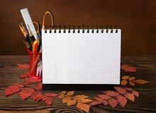 Schulausrüstung mit Bleistiften, Bürsten, Notizbuch und Herbstlaub Lizenzfreie Stockfotografie