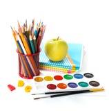 Schulausrüstung mit Bleistiften, Farben, Bürsten und Apfel Stockbild