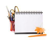 Schulausrüstung mit Bleistiften, Notizbuch und trockenem Herbstlaub Lizenzfreies Stockfoto