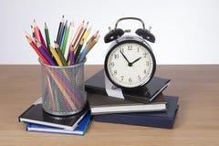 Schulbücher, Bleistiftzeichenstifte und ein Wecker Lizenzfreie Stockbilder