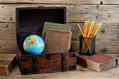 Schulbücher mit Kugel und Bleistiften im alten Kasten Stockfoto