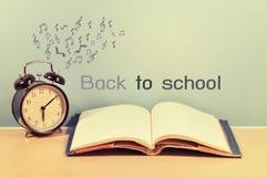 Schulbücher und Uhr mit zurück zu Schule Stockbilder