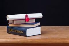 Schulbank mit Wörterbuchschwarzhintergrund Stockbild