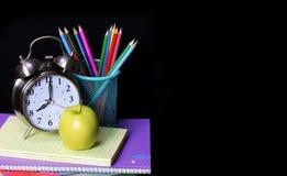 Schulbedarf über schwarzem Hintergrund Studien-Zubehör Stockbilder